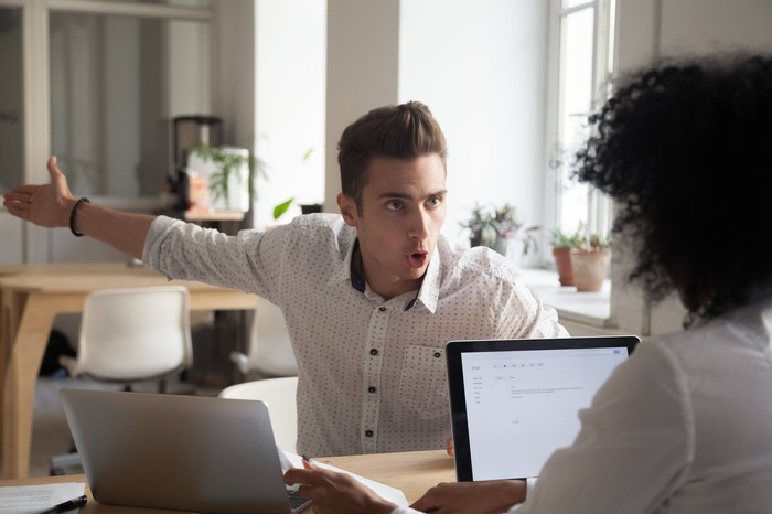 Man gesturing and yelling at a woman seated at a laptop