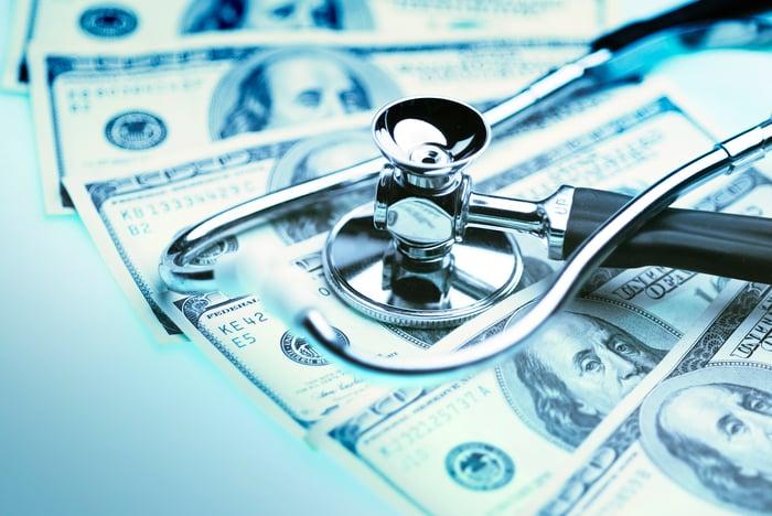A stethoscope on top of U.S. hundred-dollar bills