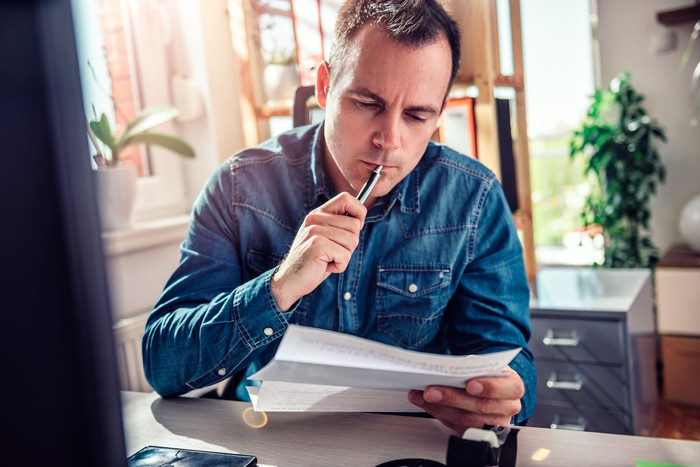 Man with thoughtful expression holding pen to lips while reading document