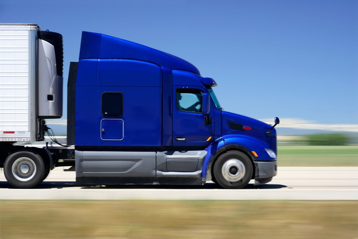 A tractor trailer with newly-painted blue cab is seen on the highway.