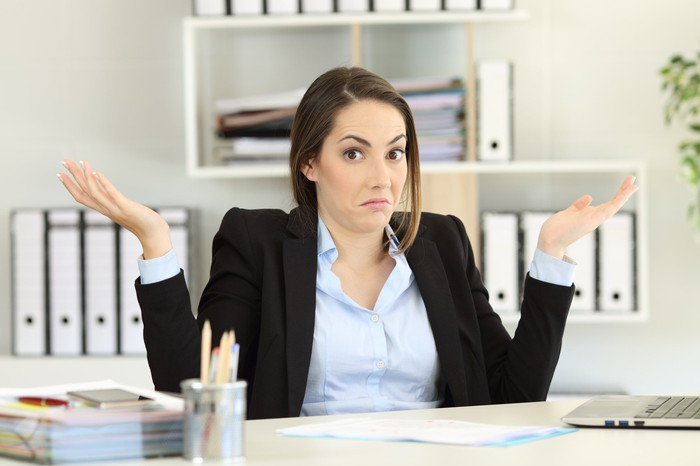 Young woman in business attire, sitting at a desk with a confused demeanor.