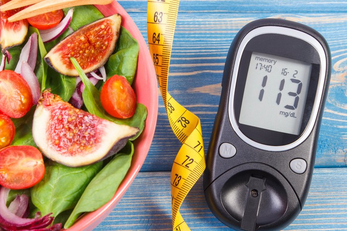A blood glucose monitor sits next to a measuring tape and a bowl of salad