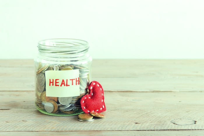 Coin-filled glass jar, sitting on wooden surface, labeled HEALTH, with red heart resting against it.