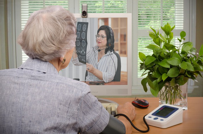 A person with a blood pressure cuff on their arm having a videoconference with a doctor.