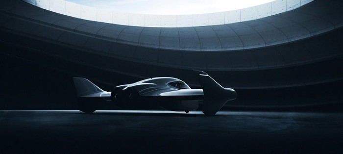 The Porsche and Boeing flying car concept, cloaked in shadow inside a futuristic looking hangar.