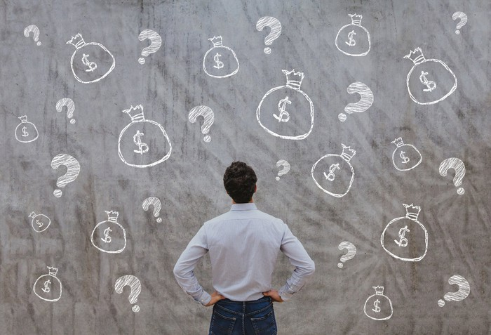 A businessman stands in front of wall with illustrations of money bags and question marks.