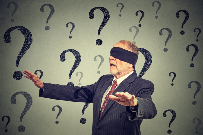 A blindfolded older businessman walks with hands outstretched, surrounded by question marks.