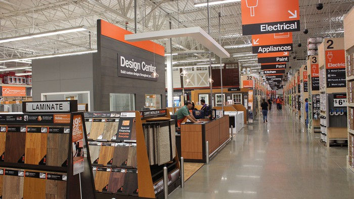 Inside of Home Depot store with flooring and design center in foreground.