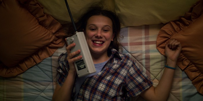 A teenage girl laying on a bed smiling while talking into a walkie-talkie