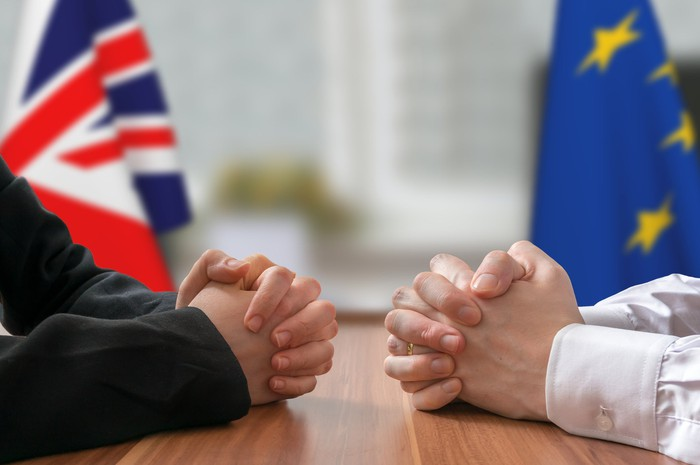 Two people sitting at a table facing each other, with a U.K. flag and a European Union flag behind them