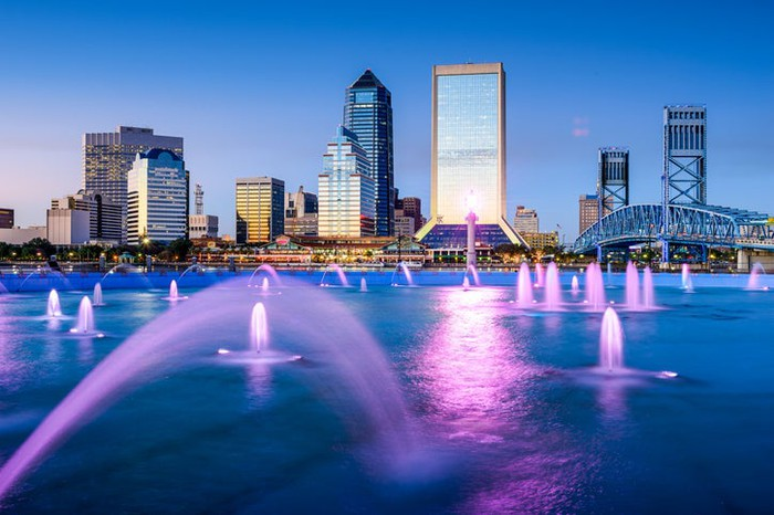 Jacksonville, Florida, skyline over St. Johns River at sunset. Numerous fountains in river shooting water up.