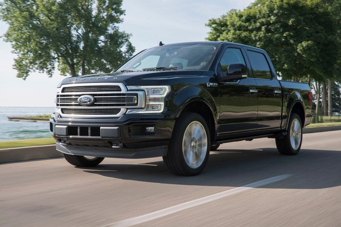 A black 2019 Ford F-150, a full size pickup truck, on a waterfront road.
