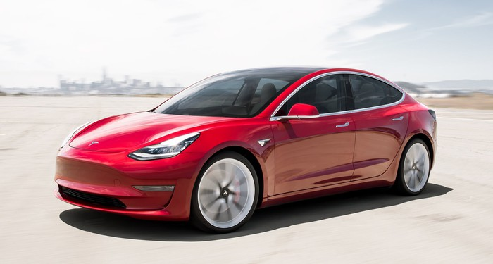 A red Tesla Model 3, a compact electric luxury-performance sedan.
