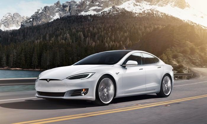A white Tesla Model S, a large electric luxury-performance sedan.