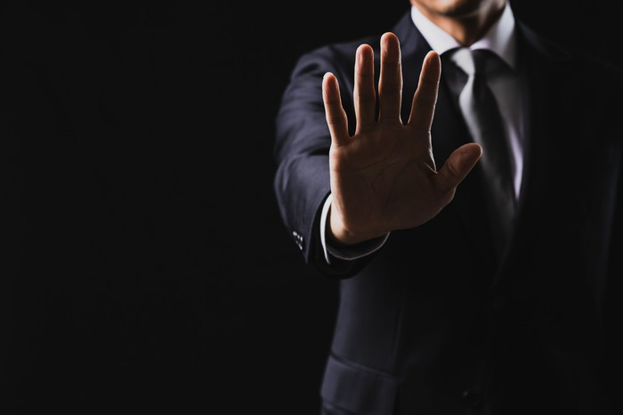 A person in a business suit raising his hand out in front of his body with his fingers outstretched