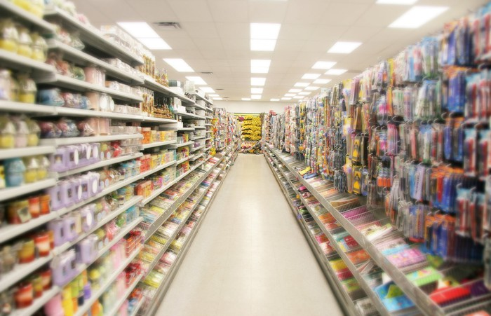 The aisle of a store with packed shelves on both sides.