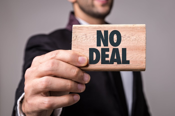 "Businessman holding piece of wood with words ""No Deal"" printing on it"
