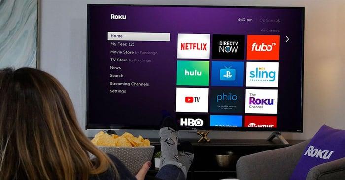 A woman facing a Roku TV.