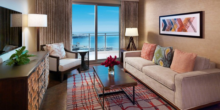 Room with couch, table, dresser, and chair, with window showing beach view.
