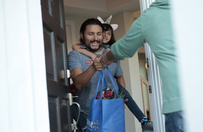 A man receiving a bag of groceries at his front door with a child on his back.