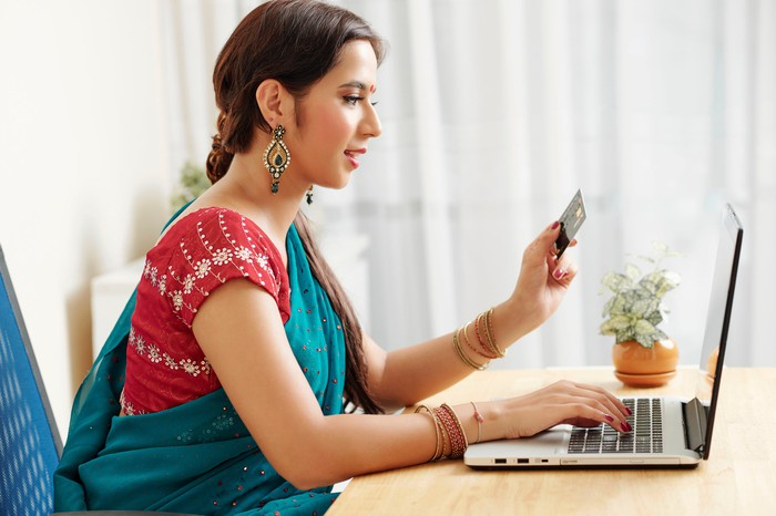 An Indian woman making an e-commerce transaction on a laptop while holding a credit card.