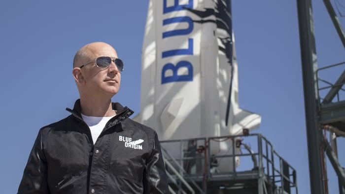 Jeff Bezos in a Blue Origin windbreaker in front of a New Shepard rocket