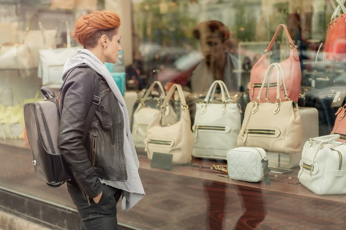 A young woman looks at handbags in a store window.