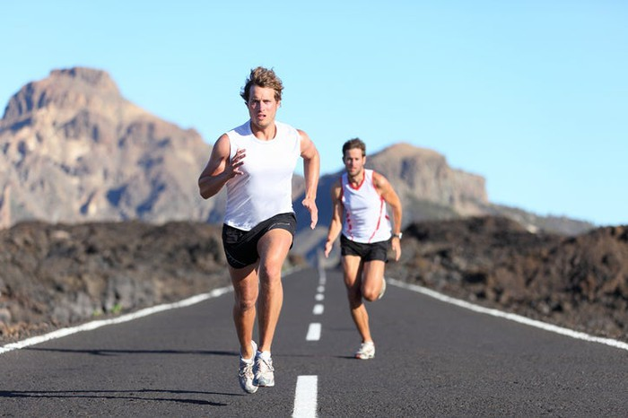 Two male runners racing on a road with cliffs and blue sky in background.