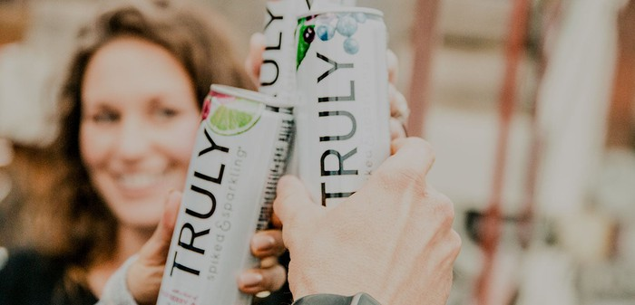 Smiling woman holding can of Truly hard seltzer.