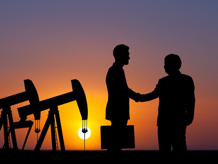 The silhouette of two men shaking hands against oil pumps at sunset.