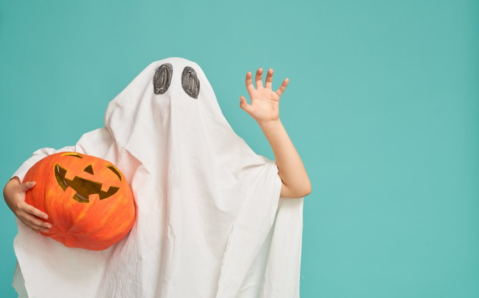 A child in a ghost costume holding a jack-o-lantern