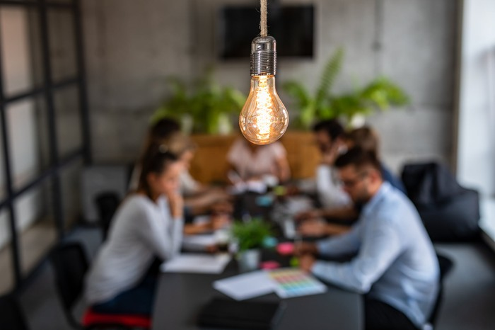 Employees brainstorm around a table at a small advertising agency, as a light bulb hangs in the foreground.