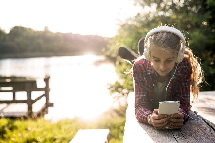 A girl laying on a picnic table near a lake, wearing headphones and using a smartphone.