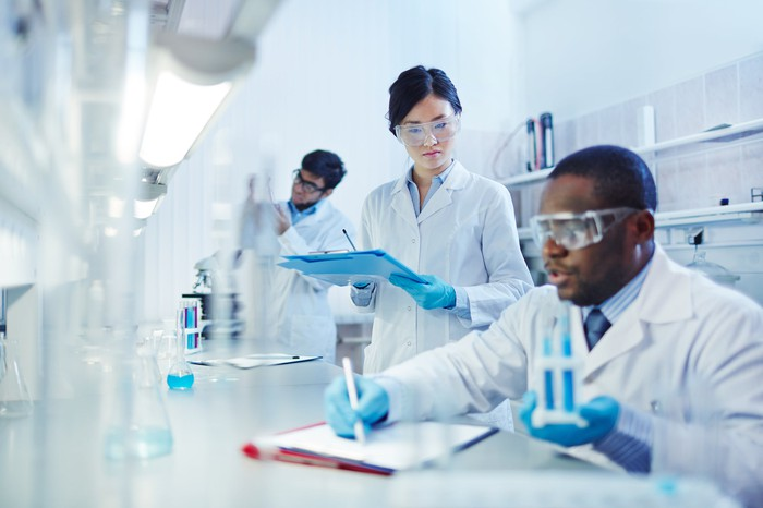 Three people in lab coats and safety goggles working in a lab.