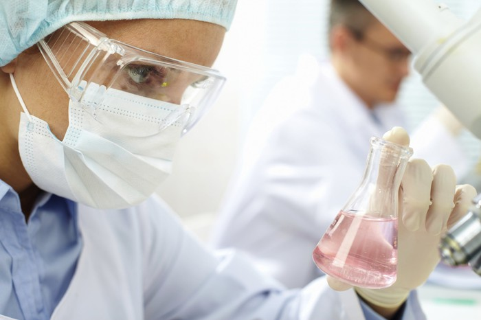 A person in a lab coat with goggles and a face mask examining a flask with liquid in it.