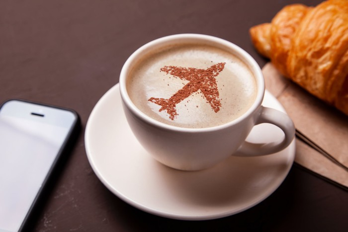 A cup of coffee with foam top that has a silhouette of an airplane on it.