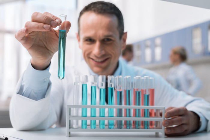 Smiling male scientist holding up a test tube with a rack of other test tubes in front of him