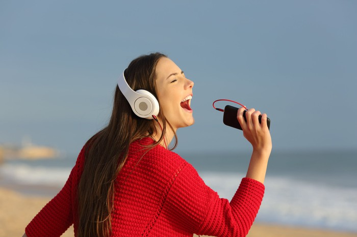 Woman singing into her phone on the beach
