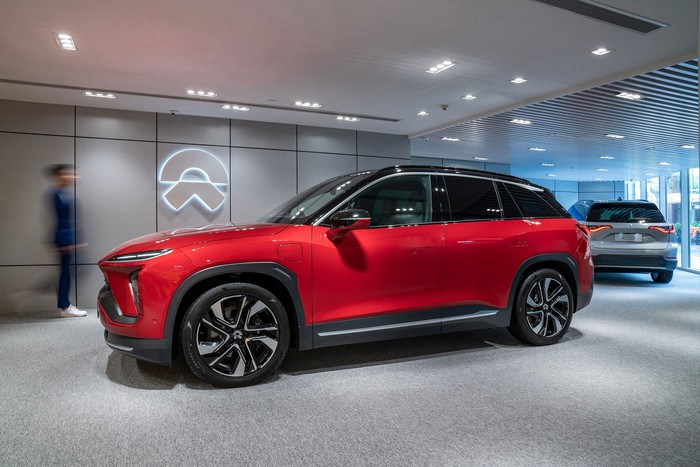 Red SUV in a showroom with the NIO logo on the wall.