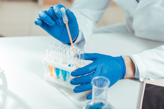 Lab technician holding an eyedropper collecting samples from test tubes.