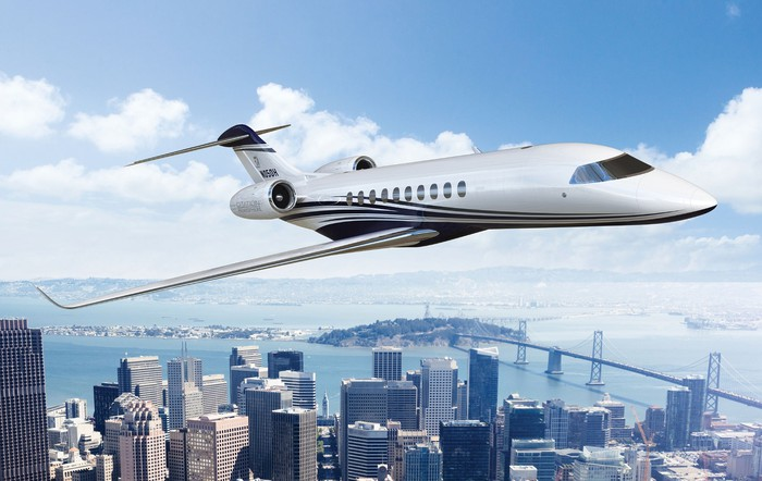 Textron Cessna jet flying with cityscape in the background.