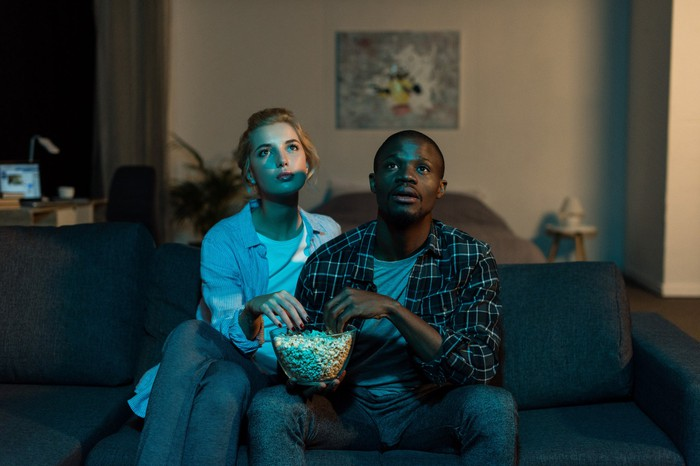 A couple sitting on the couch and eating popcorn and watching TV together at home.