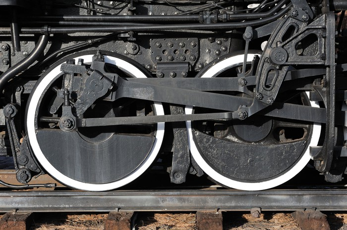 Close-up of two black locomotive wheels with white trim on a track.