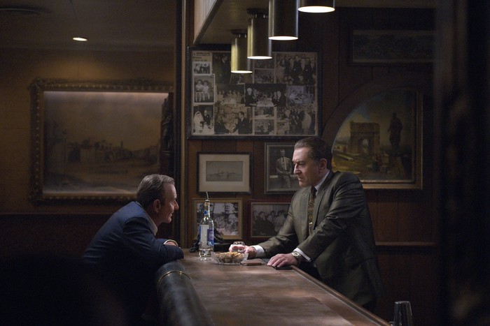 Two men in a dimly lit bar, one with a drink in hand, talking