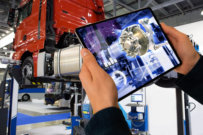 A trailer truck repair person using an augmented reality tablet device to visualize a part repair.