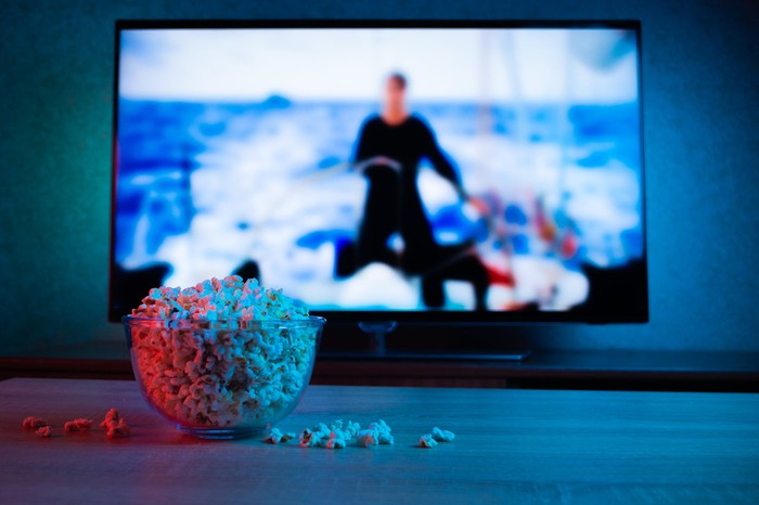 A bowl of popcorn in front of a TV