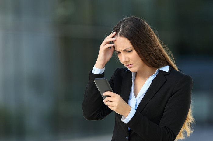 A young woman in a business suit holding her phone in one hand and frowning.