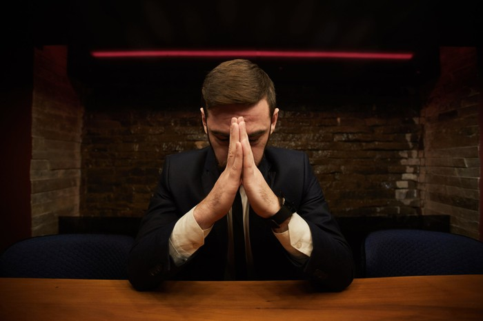 A man sitting at a table with his head bowed and his hands palm to palm in front of his face.