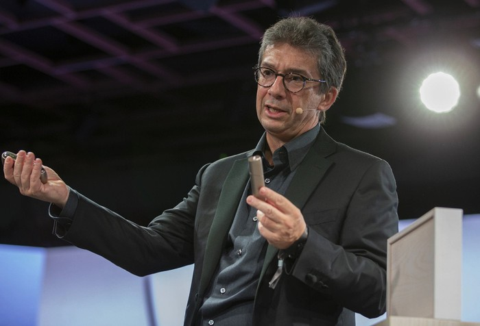 PMI CEO André Calantzopoulos holds an iQOS device.