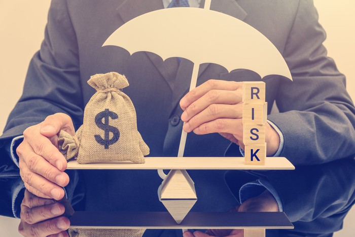 Representing the balance of risk and opportunity, a person holding a small umbrella balances two items on a fulcrum scale. On one side are bags with dollar signs on them, and on the other is a stack of letter tiles that spell out the word risk.